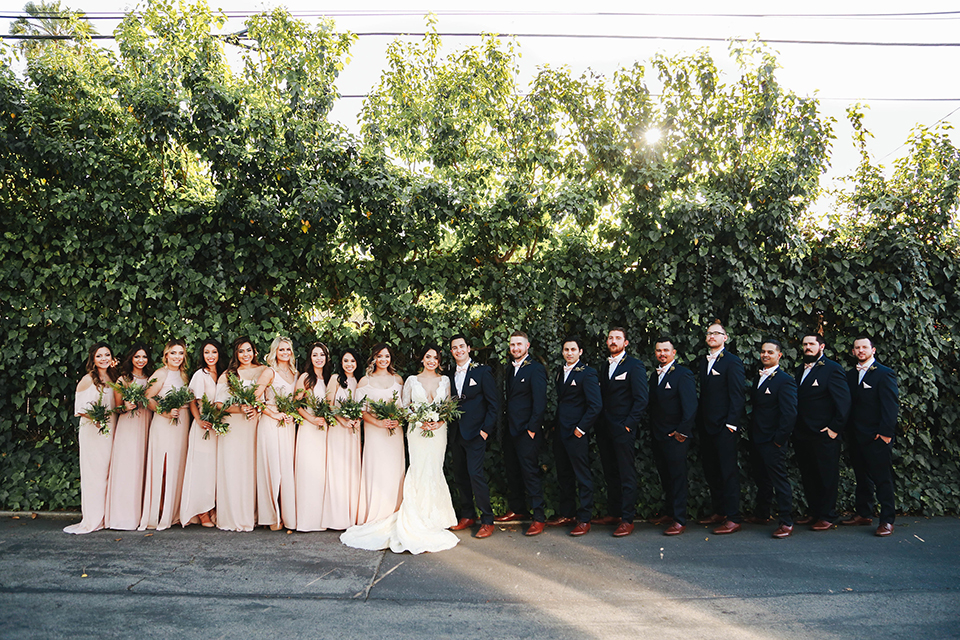 Orange county outdoor rustic wedding bride form fitting lace gown with sleeves and plunging neckline with groom navy blue notch lapel suit with white dress shirt and blush pink bow tie with matching pocket square and whit and green floral boutonniere with bridesmaids long blush pink dresses and groomsmen navy blue suits with blush pink bow ties