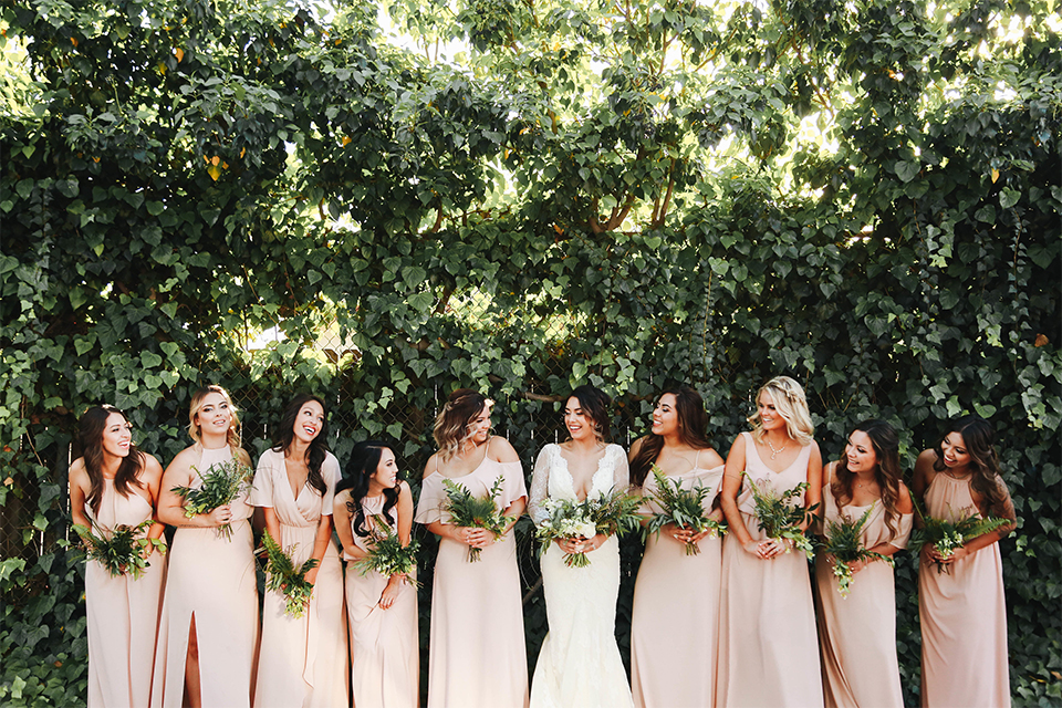 Orange county outdoor rustic wedding bride form fitting lace gown with sleeves and plunging neckline holding green and white floral bridal bouquet with bridesmaids long blush pink dresses holding white and green floral bouquets