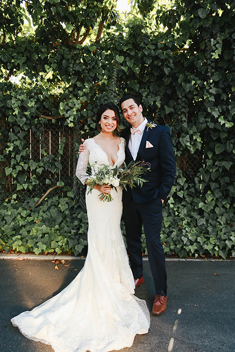Orange county outdoor rustic wedding bride form fitting lace gown with sleeves and plunging neckline with groom navy blue notch lapel suit with white dress shirt and blush pink bow tie with matching pocket square and whit and green floral boutonniere bride holding green and white floral bridal bouquet