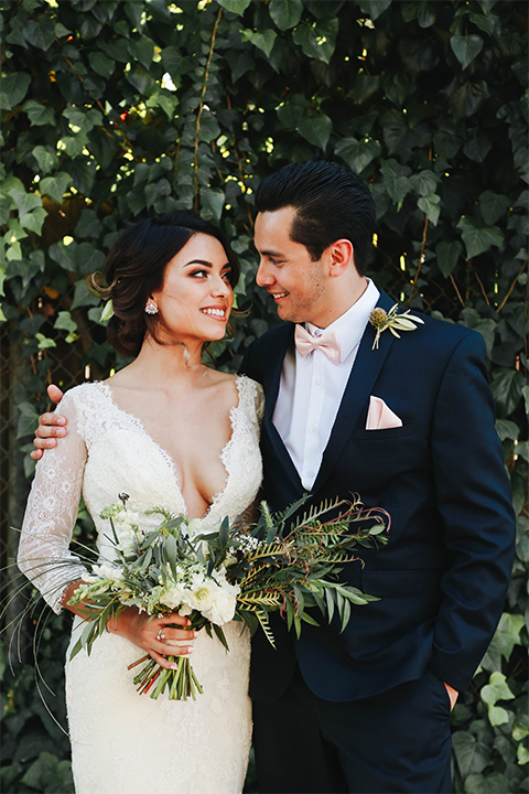 Orange county outdoor rustic wedding bride form fitting lace gown with sleeves and plunging neckline with groom navy blue notch lapel suit with white dress shirt and blush pink bow tie with matching pocket square and whit and green floral boutonniere hugging and bride holding green and white floral bridal bouquet