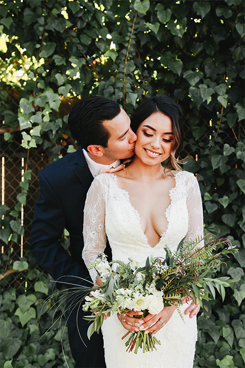 Orange county outdoor rustic wedding bride form fitting lace gown with sleeves and plunging neckline with groom navy blue notch lapel suit with white dress shirt and blush pink bow tie with matching pocket square and whit and green floral boutonniere kissing bride on cheek and bride holding green and white floral bridal bouquet