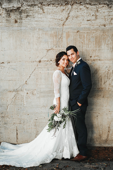 Orange county outdoor rustic wedding bride form fitting lace gown with sleeves and plunging neckline with groom navy blue notch lapel suit with white dress shirt and blush pink bow tie with matching pocket square and whit and green floral boutonniere standing and hugging and bride holding green and white floral bridal bouquet