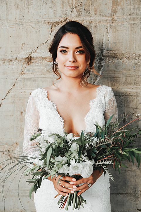 Orange county outdoor rustic wedding bride form fitting lace gown with sleeves and plunging neckline holding green and white floral bridal bouquet smiling