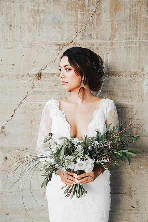 Orange county outdoor rustic wedding bride form fitting lace gown with sleeves and plunging neckline holding green and white floral bridal bouquet looking away