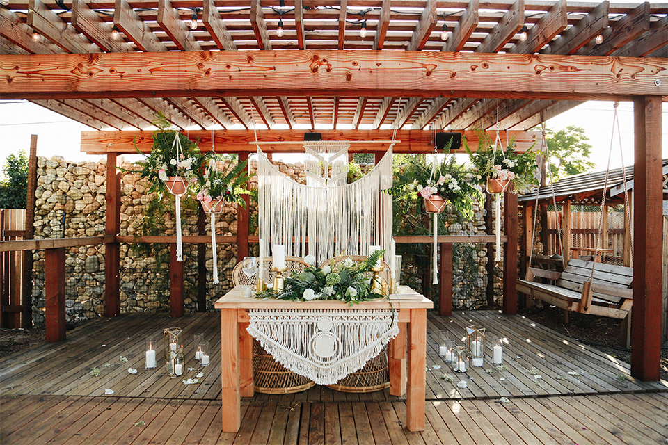 Orange county outdoor rustic wedding at the riverbed farm sweetheart table set up light brown wood table with hanging white decor in background and green and white flower centerpiece decor with hanging flowers and white lace table linen wedding photo idea