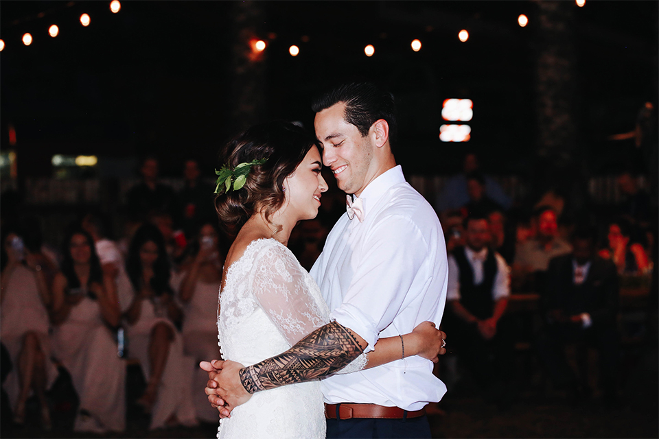 Orange county outdoor rustic wedding bride form fitting lace gown with sleeves and plunging neckline with groom navy blue notch lapel suit with white dress shirt and blush pink bow tie with matching pocket square and whit and green floral boutonniere first dance at reception
