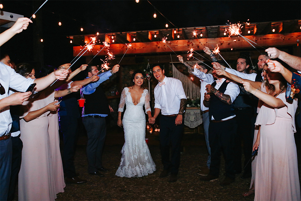 Orange county outdoor rustic wedding bride form fitting lace gown with sleeves and plunging neckline with groom navy blue notch lapel suit with white dress shirt and blush pink bow tie with matching pocket square and whit and green floral boutonniere sparkler exit