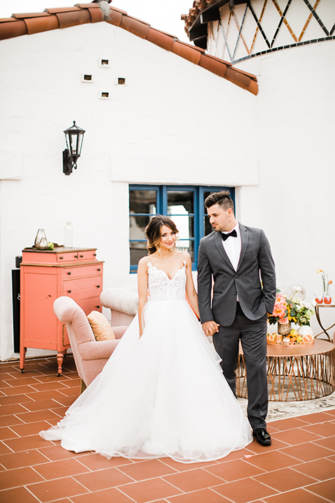 Orange county beach wedding at ole hanson beach club bride ball gown with thin straps and sweetheart neckline with low back design and lace details with groom charcoal grey tuxedo with white dress shirt and black bow tie holding hands and smiling