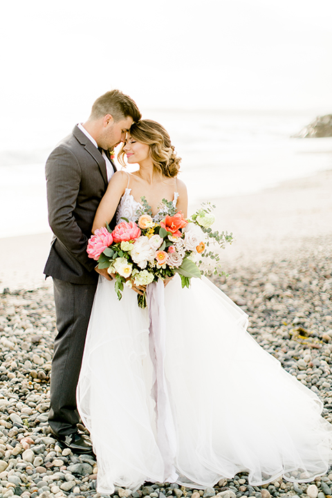 Orange county beach wedding at ole hanson beach club bride ball gown with thin straps and sweetheart neckline with low back design and lace details with groom charcoal grey tuxedo with white dress shirt and black bow tie hugging and bride holding pink and orange floral bridal bouquet with ribbon decor