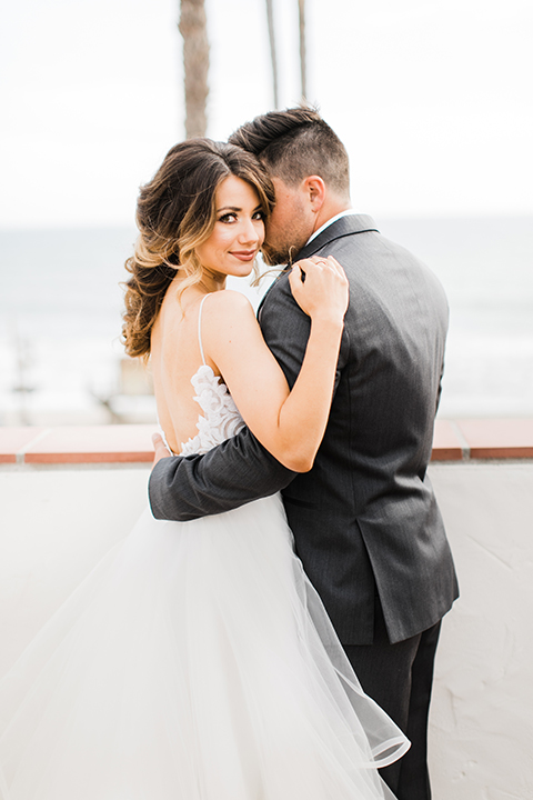 Orange county beach wedding at ole hanson beach club bride ball gown with thin straps and sweetheart neckline with low back design and lace details with groom charcoal grey tuxedo with white dress shirt and black bow tie hugging