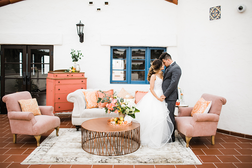 Orange county beach wedding at ole hanson beach club bride ball gown with thin straps and sweetheart neckline with low back design and lace details with groom charcoal grey tuxedo with white dress shirt and black bow tie standing by lounge furniture hugging and holding hands