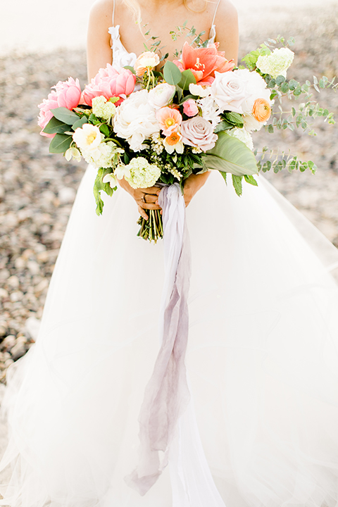 Orange county beach wedding at ole hanson beach club bride ball gown with thin straps and sweetheart neckline with low back design and lace details holding pink and orange floral bridal bouquet close up