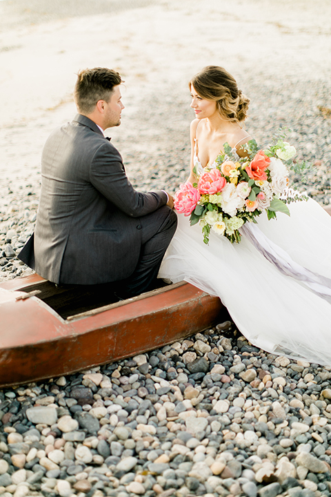 Orange county beach wedding at ole hanson beach club bride ball gown with thin straps and sweetheart neckline with low back design and lace details with groom charcoal grey tuxedo with white dress shirt and black bow tie sitting in boat bride holding pink and orange floral bridal bouquet