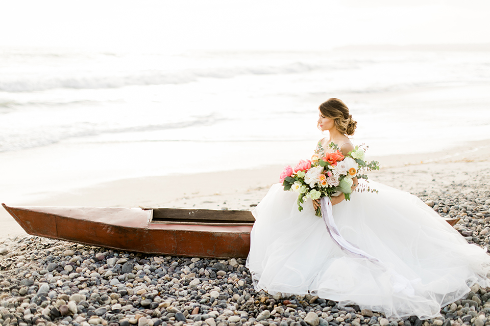 Orange county beach wedding at ole hanson beach club bride ball gown with thin straps and sweetheart neckline with low back design and lace details holding pink and orange floral bridal bouquet close up sitting in boat