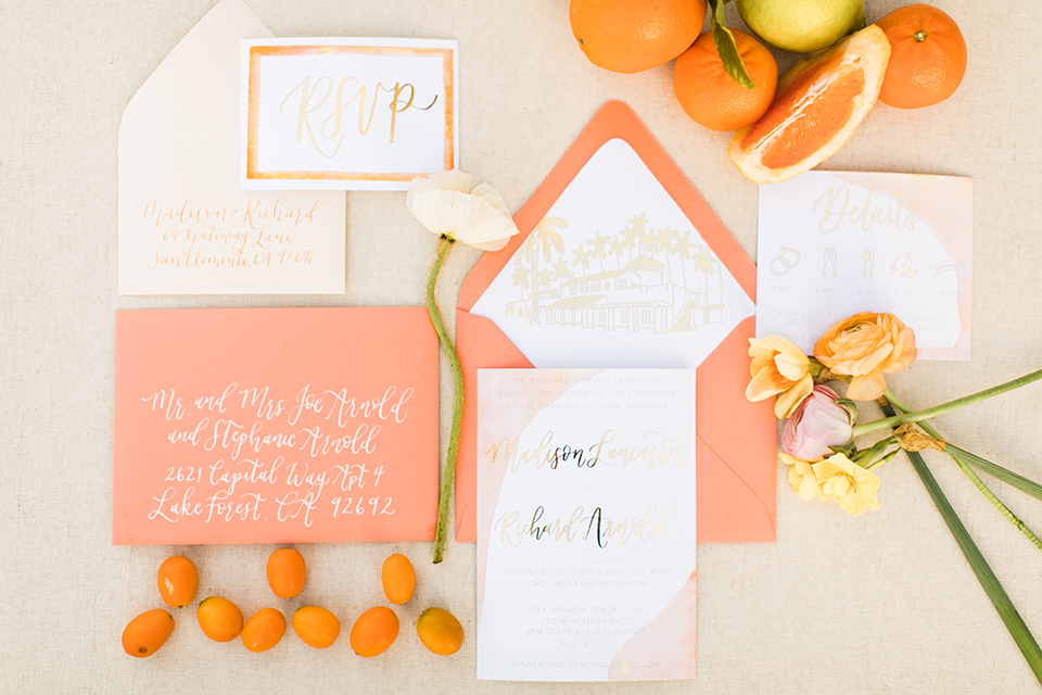 Orange county beach wedding at ole hanson beach club wedding invitations orange and white invitations with gold calligraphy writing and oranges fruit decor with white flowers on light background wedding photo idea for invitations