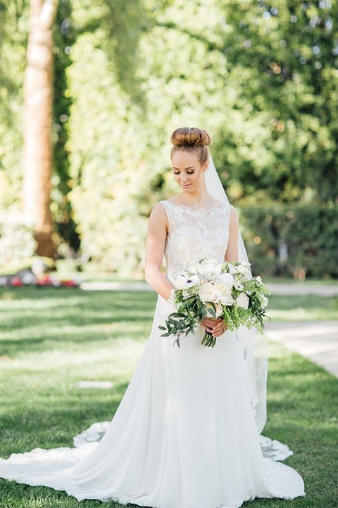 Orange county nautical navy wedding at the nixon library bride chiffon gown with lace bodice and high neckline with hair in bun and long veil holding white and green floral bridal bouquet