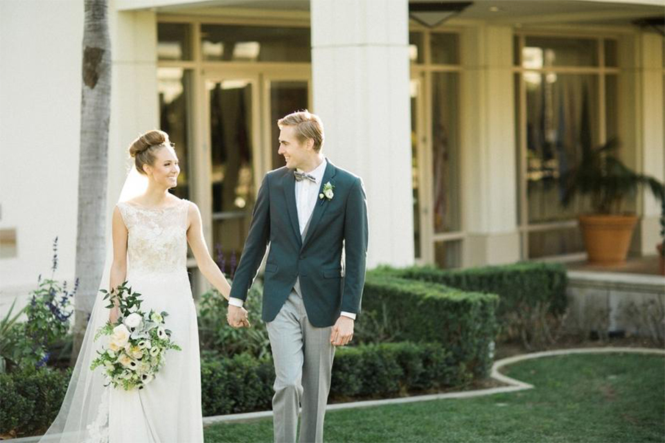 Orange county nautical navy wedding at the nixon library bride chiffon gown with lace bodice and high neckline with hair in bun and long veil with groom slate blue coat with heather grey pants and matching vest with white dress shirt and heather grey pipe edge bow tie and white floral boutonniere walking and holding hands bride holding white and green floral bridal bouquet