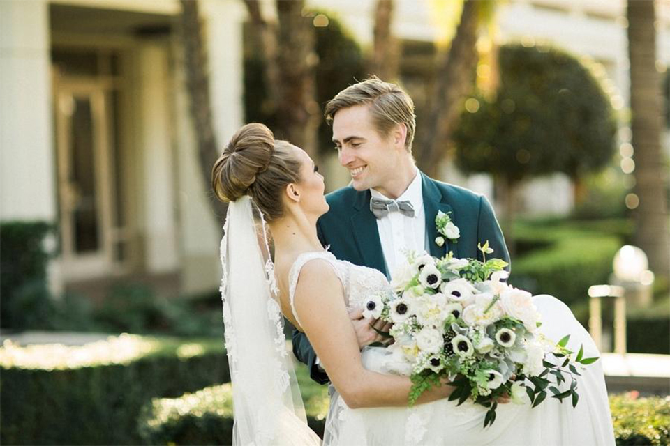 Orange county nautical navy wedding at the nixon library bride chiffon gown with lace bodice and high neckline with hair in bun and long veil with groom slate blue coat with heather grey pants and matching vest with white dress shirt and heather grey pipe edge bow tie and white floral boutonniere groom carrying bride holding white and green floral bridal bouquet