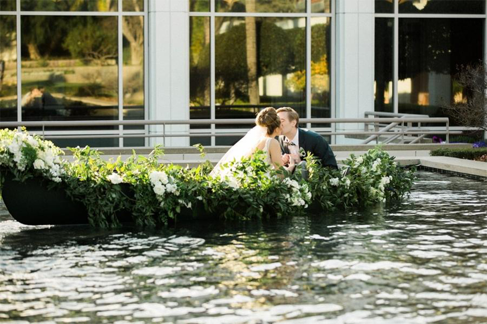 Orange county nautical navy wedding at the nixon library bride chiffon gown with lace bodice and high neckline with hair in bun and long veil with groom slate blue coat with heather grey pants and matching vest with white dress shirt and heather grey pipe edge bow tie and white floral boutonniere kissing on boat with greenery floral decor