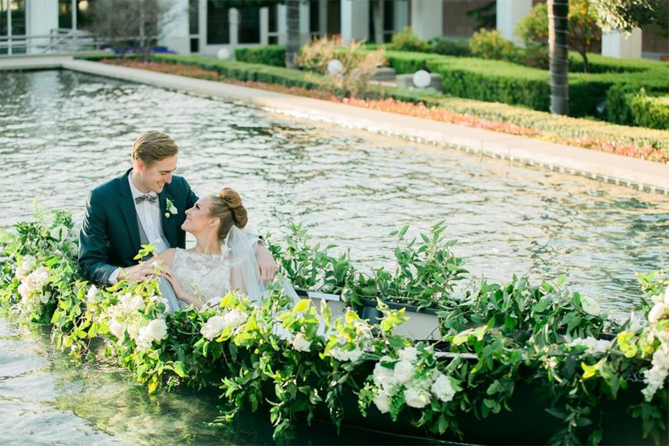 Orange county nautical navy wedding at the nixon library bride chiffon gown with lace bodice and high neckline with hair in bun and long veil with groom slate blue coat with heather grey pants and matching vest with white dress shirt and heather grey pipe edge bow tie and white floral boutonniere sitting on boat with greenery floral decor
