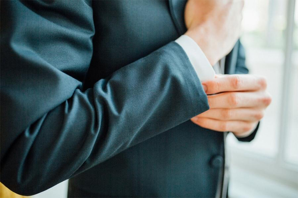 Orange county nautical navy wedding at the nixon library groom slate blue suit coat with heather grey suit pants and matching vest with white dress shirt and matching heather grey pipe edge bow tie and white floral boutonniere fixing sleeve close up