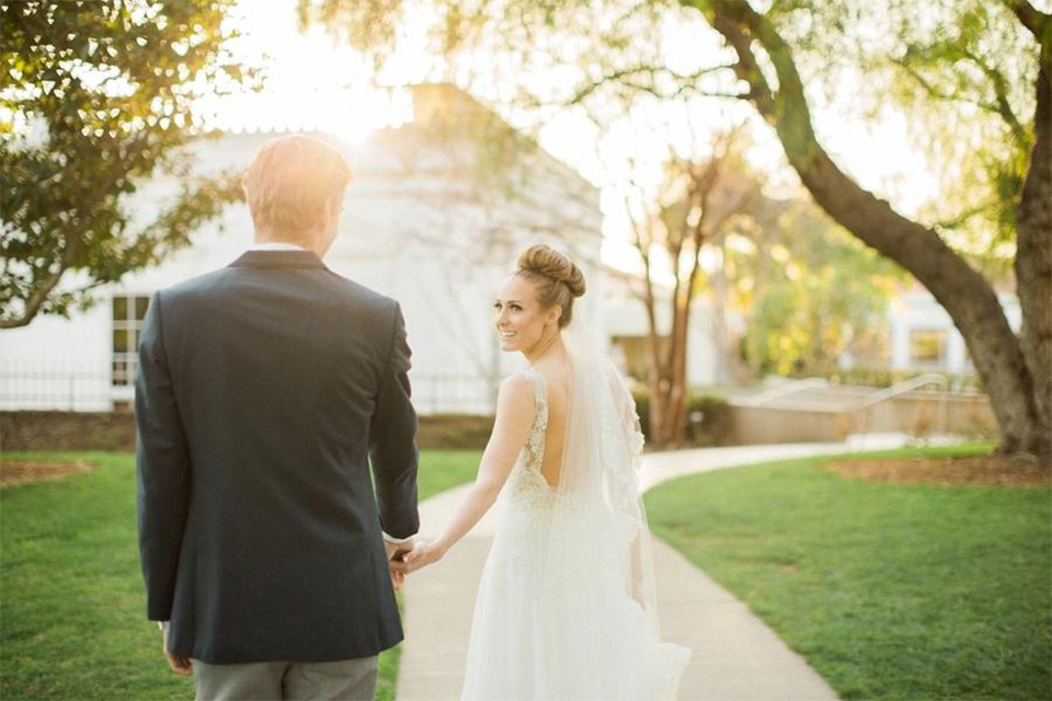 Orange county nautical navy wedding at the nixon library bride chiffon gown with lace bodice and high neckline with hair in bun and long veil with groom slate blue coat with heather grey pants and matching vest with white dress shirt and heather grey pipe edge bow tie and white floral boutonniere walking and holding hands bride holding white and green floral bridal bouquet at sunset