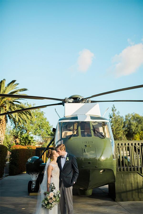 Orange county nautical navy wedding at the nixon library bride chiffon gown with lace bodice and high neckline with hair in bun and long veil with groom slate blue coat with heather grey pants and matching vest with white dress shirt and heather grey pipe edge bow tie and white floral boutonniere standing by helicopter kissing