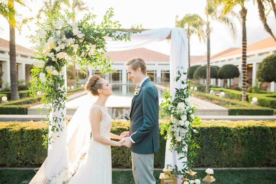 Orange county nautical navy wedding at the nixon library bride chiffon gown with lace bodice and high neckline with hair in bun and long veil with groom slate blue coat with heather grey pants and matching vest with white dress shirt and heather grey pipe edge bow tie and white floral boutonniere holding hands standing by ceremony arch during ceremony
