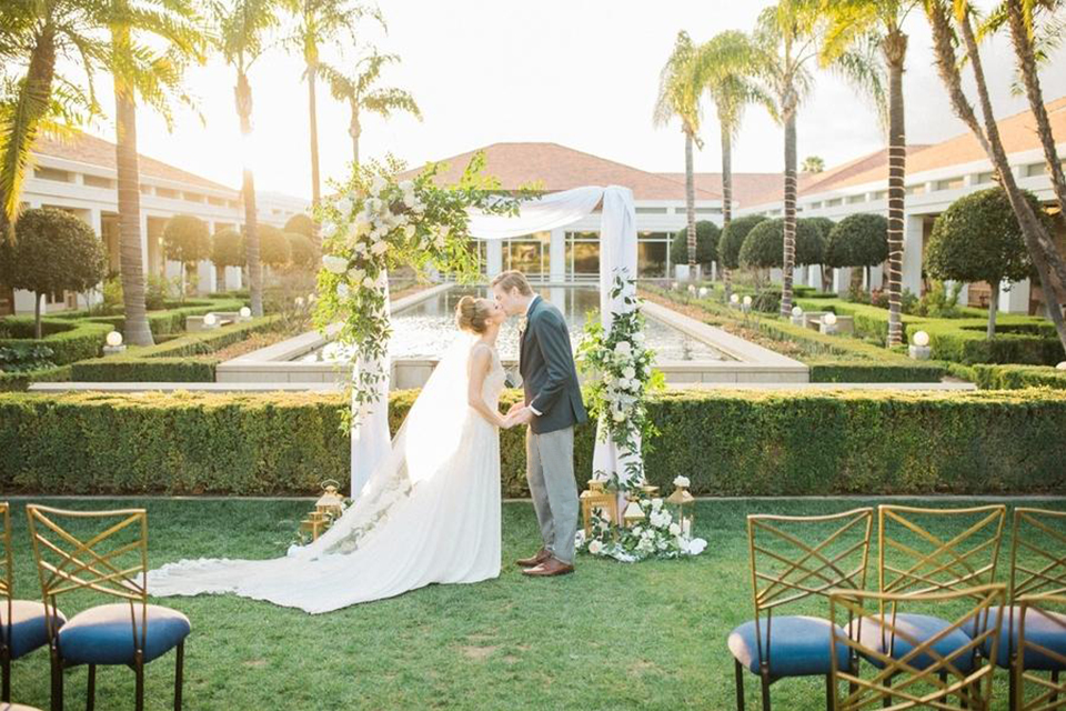Orange county nautical navy wedding at the nixon library bride chiffon gown with lace bodice and high neckline with hair in bun and long veil with groom slate blue coat with heather grey pants and matching vest with white dress shirt and heather grey pipe edge bow tie and white floral boutonniere kissing during ceremony standing by arch with white chiffon and floral decor