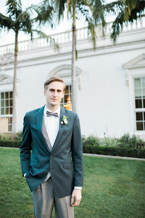 Orange county nautical navy wedding at the nixon library groom slate blue suit coat with heather grey suit pants and matching vest with white dress shirt and matching heather grey pipe edge bow tie and white floral boutonniere