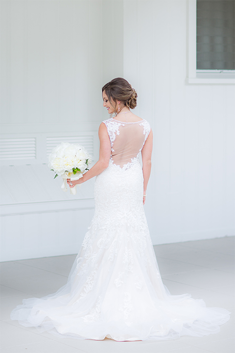 San diego wedding at the crossings carlsbad bride form fitting lace gown with thin straps and ruffled skirt with sweetheart neckline holding white floral bridal bouquet