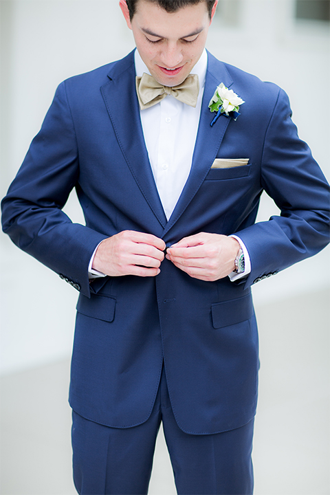San diego wedding at the crossings carlsbad groom cobalt blue suit with white dress shirt and gold bow tie with matching pocket square and white floral boutonniere buttoning jacket