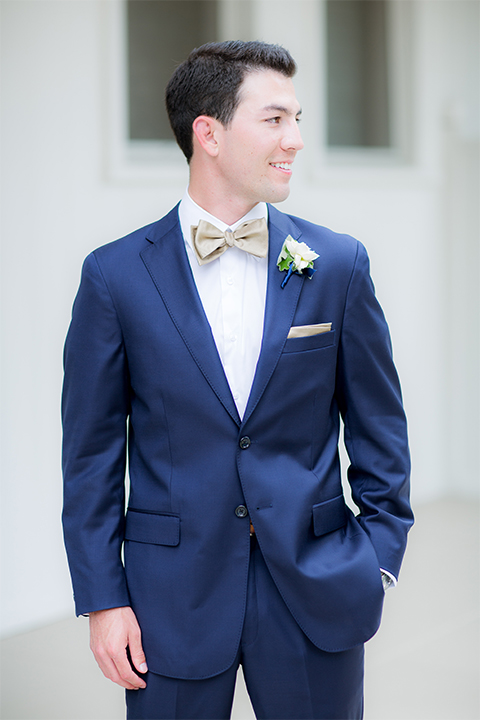 San diego wedding at the crossings carlsbad groom cobalt blue suit with white dress shirt and gold bow tie with matching pocket square and white floral boutonniere
