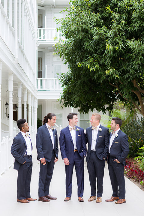 San diego wedding at the crossings carlsbad groom cobalt blue suit with white dress shirt and gold bow tie with matching pocket square and white floral boutonniere with groomsmen grey suits with white dress shirts and bow ties