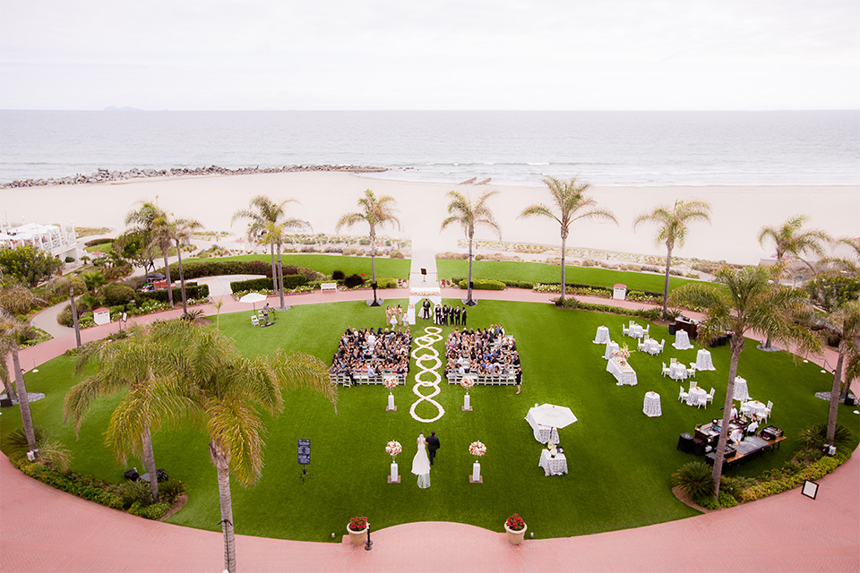 San diego wedding at the crossings carlsbad bride form fitting lace gown with thin straps and ruffled skirt with sweetheart neckline holding white floral bridal bouquet walking down the aisle with dad far away view of venue with palm trees in background wedding photo idea for ceremony