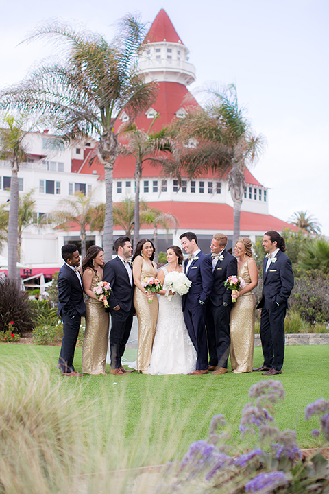 San diego wedding at the crossings carlsbad bride form fitting lace gown with thin straps and ruffled skirt with sweetheart neckline and long veil with groom cobalt blue suit with white dress shirt and gold bow tie with matching pocket square and white floral boutonniere with bridesmaids long gold sequined dresses and groomsmen grey suits with white dress shirts and bow ties