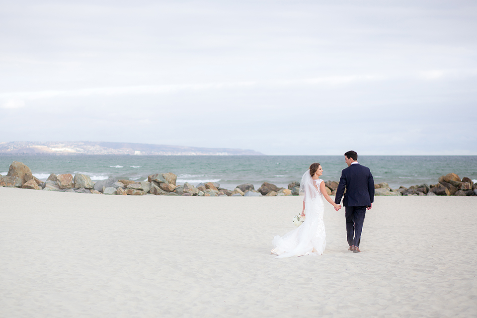 San diego wedding at the crossings carlsbad bride form fitting lace gown with thin straps and ruffled skirt with sweetheart neckline and long veil with groom cobalt blue suit with white dress shirt and gold bow tie with matching pocket square and white floral boutonniere holding hands and walking on the beach