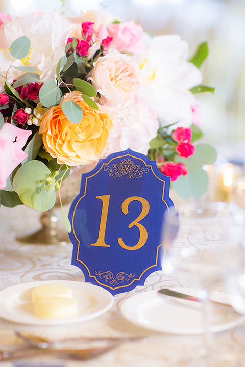 San diego wedding at the crossings carlsbad table set up with white table linen and gold chairs with white and pink flower centerpiece decor with white place settings and candle decor with blue and gold table numbers