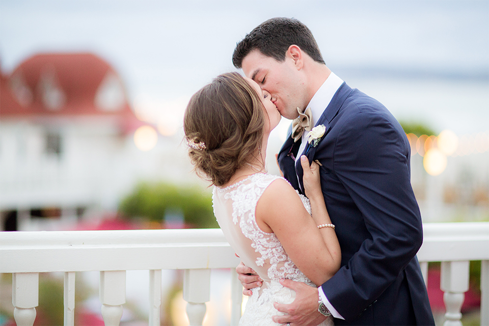 San diego wedding at the crossings carlsbad bride form fitting lace gown with thin straps and ruffled skirt with sweetheart neckline and long veil with groom cobalt blue suit with white dress shirt and gold bow tie with matching pocket square and white floral boutonniere kissing