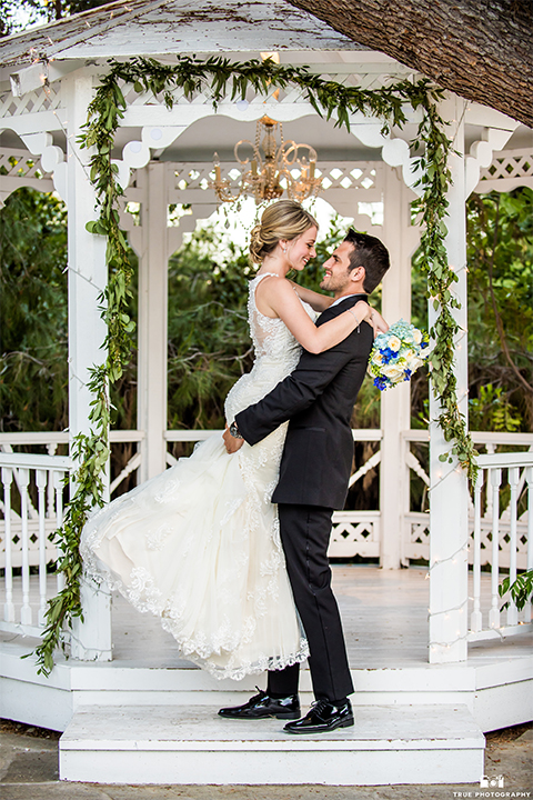 San diego wedding at green gables estate bride form fitting lace gown with a long train and high illusion neckline with long veil and groom black shawl lapel tuxedo with matching vest and white dress shirt with long black skinny tie and white floral boutonniere hugging and smiling