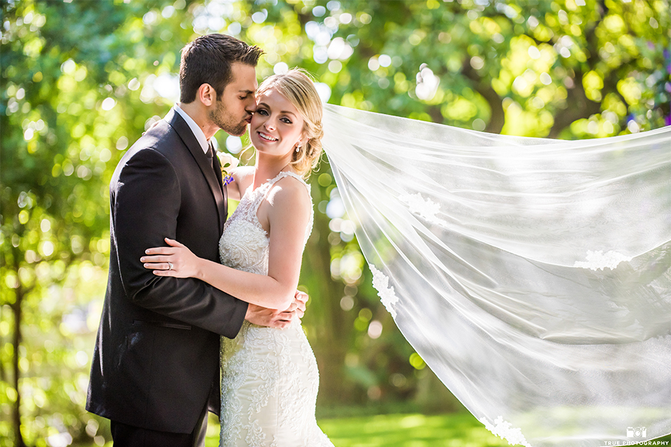 San diego wedding at green gables estate bride form fitting lace gown with a long train and high illusion neckline with long veil and groom black shawl lapel tuxedo with matching vest and white dress shirt with long black skinny tie and white floral boutonniere hugging and kissing
