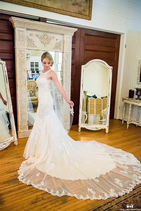 San diego wedding at green gables estate bride form fitting lace gown with a long train and high illusion neckline with long veil holding white and blue floral bridal bouquet