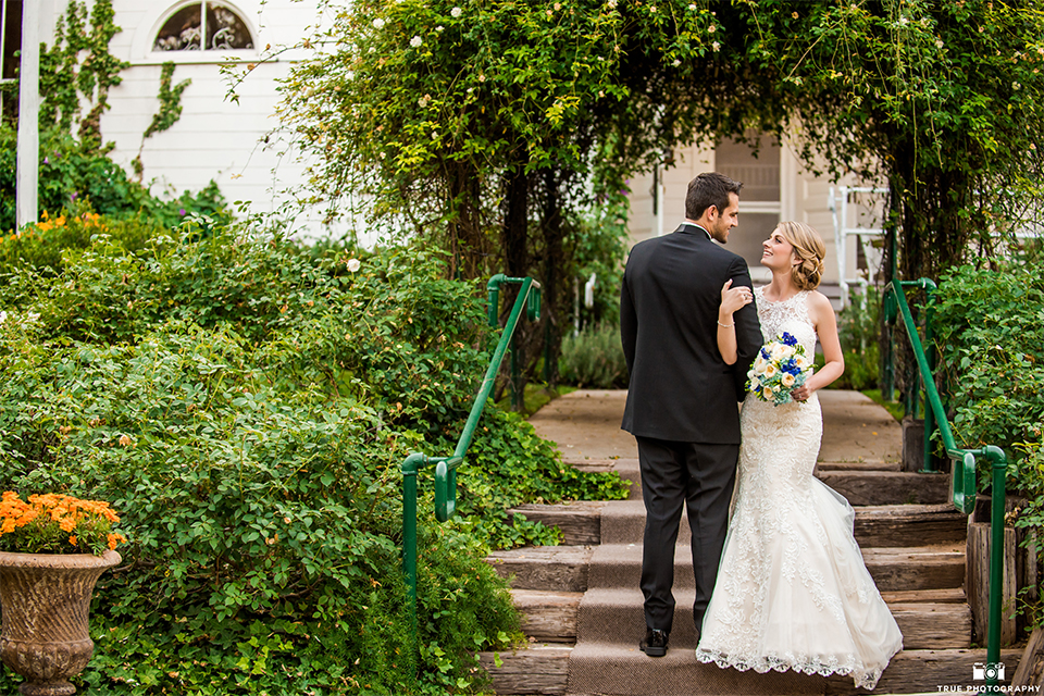 San diego wedding at green gables estate bride form fitting lace gown with a long train and high illusion neckline with long veil and groom black shawl lapel tuxedo with matching vest and white dress shirt with long black skinny tie and white floral boutonniere hugging and holding arm