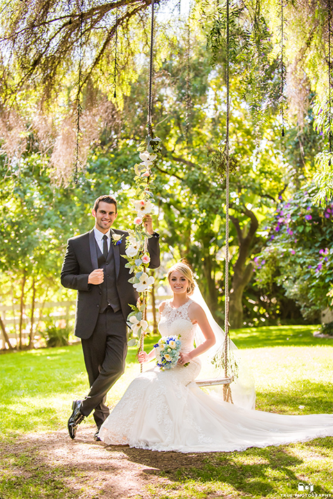 San diego wedding at green gables estate bride form fitting lace gown with a long train and high illusion neckline with long veil and groom black shawl lapel tuxedo with matching vest and white dress shirt with long black skinny tie and white floral boutonniere bride sitting on swing and groom standing