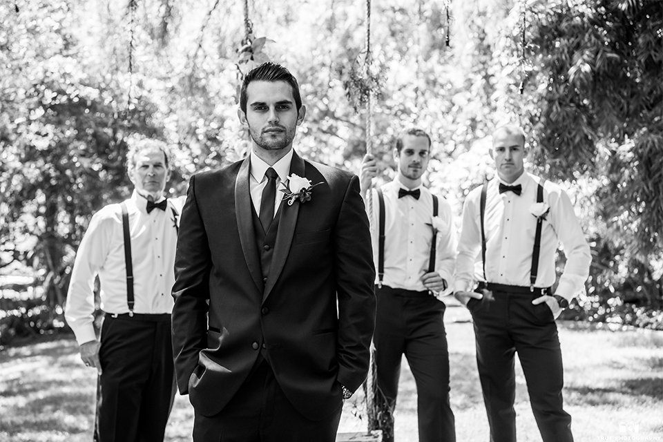 San diego wedding at green gables estate groom black shawl lapel tuxedo with matching vest and white dress shirt with long black skinny tie and white floral boutonniere with groomsmen bow ties and suspenders black and white photo