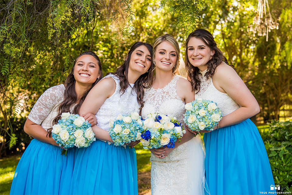 San diego wedding at green gables estate bride form fitting lace gown with a long train and high illusion neckline with long veil holding white and blue floral bridal bouquet with bridesmaids white and blue dresses holding white and blue floral bridal bouquets
