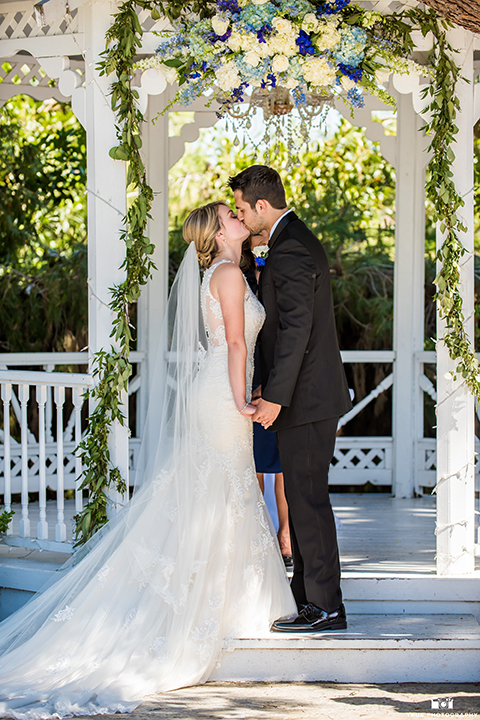 San diego wedding at green gables estate bride form fitting lace gown with a long train and high illusion neckline with long veil and groom black shawl lapel tuxedo with matching vest and white dress shirt with long black skinny tie and white floral boutonniere holding hands and kissing during ceremony