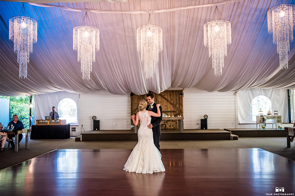 San diego wedding at green gables estate bride form fitting lace gown with a long train and high illusion neckline with long veil and groom black shawl lapel tuxedo with matching vest and white dress shirt with long black skinny tie and white floral boutonniere first dance