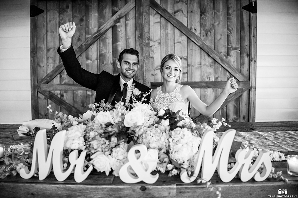 San diego wedding at green gables estate bride form fitting lace gown with a long train and high illusion neckline with long veil and groom black shawl lapel tuxedo with matching vest and white dress shirt with long black skinny tie and white floral boutonniere sweetheart table black and white photo