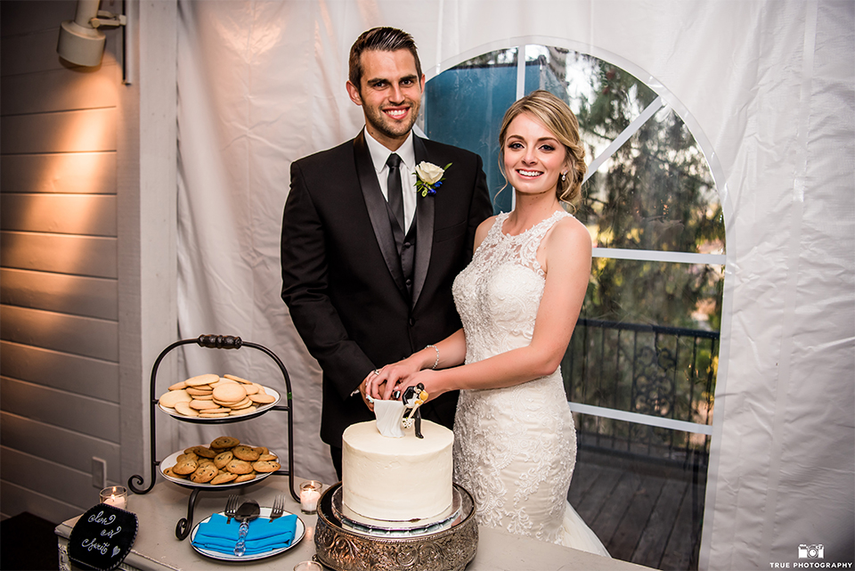 San diego wedding at green gables estate bride form fitting lace gown with a long train and high illusion neckline with long veil and groom black shawl lapel tuxedo with matching vest and white dress shirt with long black skinny tie and white floral boutonniere cutting cake and smiling